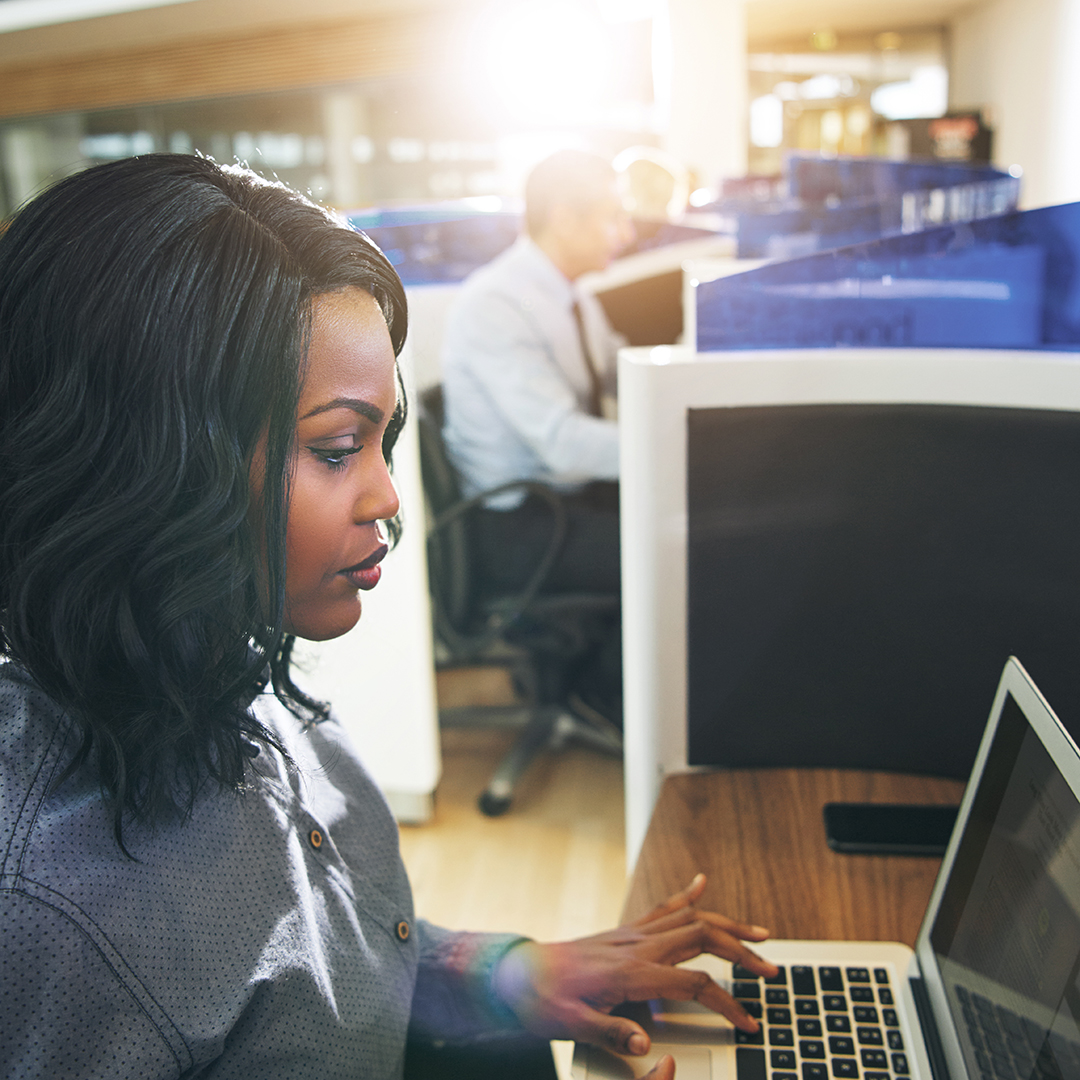 young-black-woman-typing-laptop-at-workplace-in-office